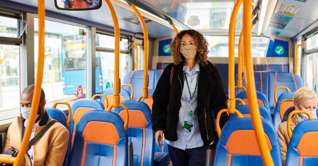 Mask Transit: A nurse, wearing her mask, maintains physical distance on transit.