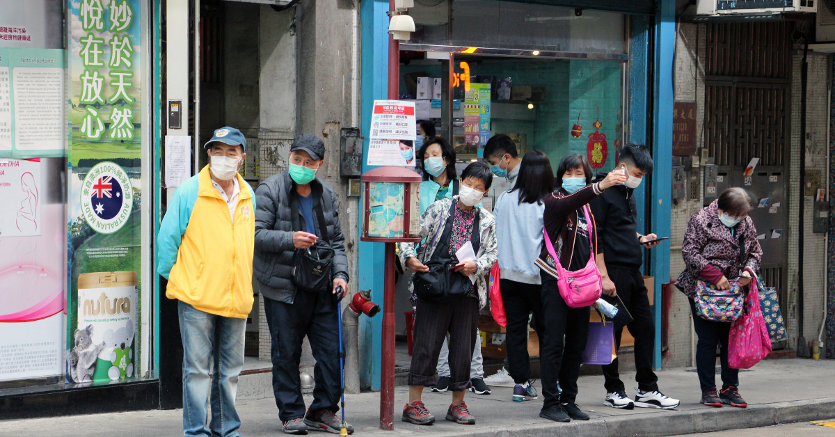 People waiting at a bus stop in Macau. Photo by Macau Photo Agency.