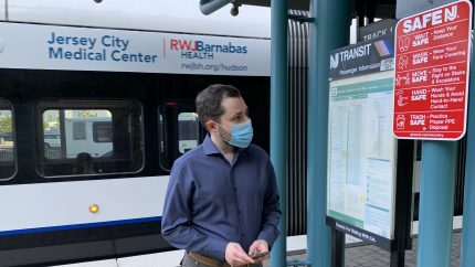Stewart Mader inspects Safe NJ signs at the Port Imperial bus and light rail station in New Jersey.