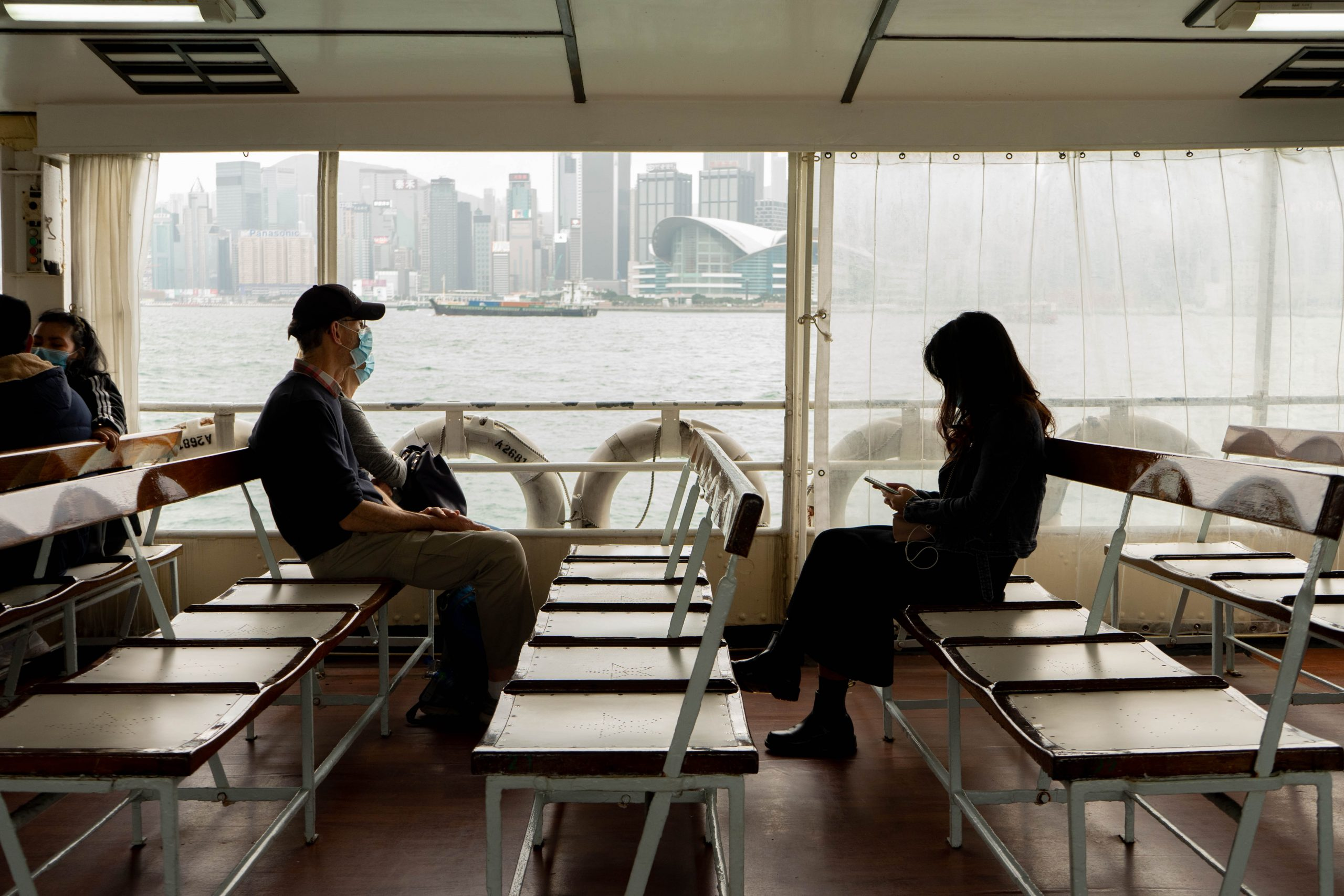 People wear masks and maintain physical distance while riding a ferry. Photo by Big Dodzy.