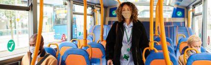 Mask Transit: A nurse, wearing her mask, maintains physical distance on transit.
